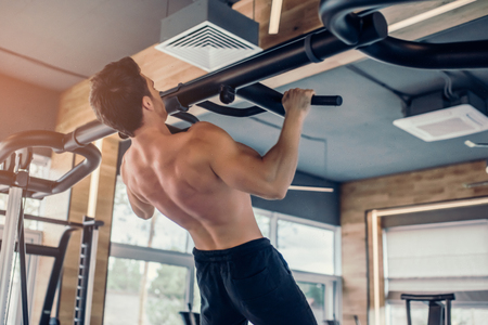 Handsome muscular man is training in gym. Sports man is doing pull ups shirtless.