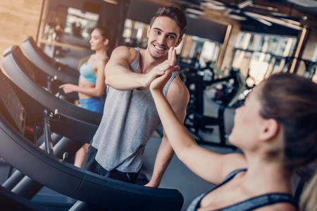 Sports people on running track. Two attractive young women and handsome muscular man are running in gym.  Treadmills.