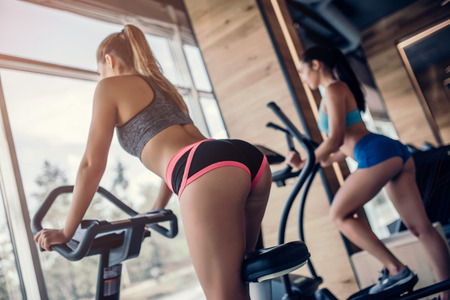 Two attractive sports women on exercise bike. Girls cycling on training apparatus.