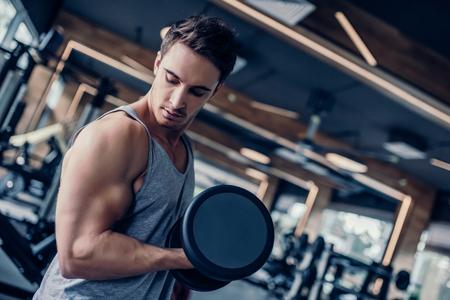 Handsome muscular man is training in gym. Sports man with dumbbells Lizenzfreie Bilder