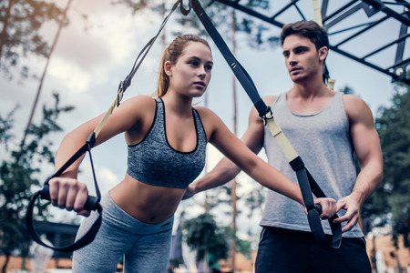 Young couple are training outdoor on TRX. Total Body Resistance Exercises. Attractive woman is working out at gym with handsome trainer. Lizenzfreie Bilder