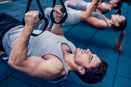 Group of sports people are training outdoors with TRX. Total Body Resistance Exercises. Two attractive young women and handsome man are working out in gym.