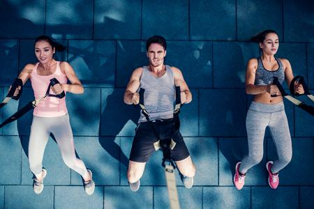スポーツの人々のグループのトップビューは TRX と屋外で訓練されています。総ボディ抵抗の練習。2人の魅力的な若い女性とハンサムな男性がジム 写真素材