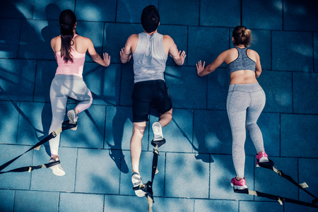 Top view of group of sports people are training outdoors with TRX. Total Body Resistance Exercises. Two attractive young women and handsome man are working out in gym.