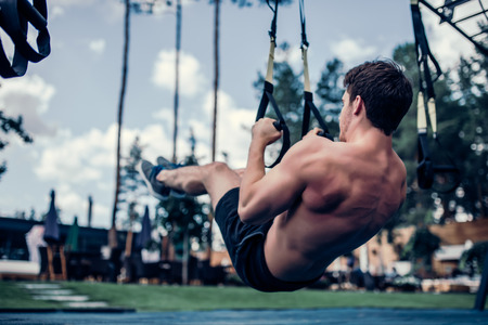 Handsome muscular man is training outdoor on TRX. Total Body Resistance Exercises. Working out at gym.