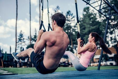 Pareja joven está entrenando al aire libre en TRX. Ejercicios de resistencia total del cuerpo. La mujer atractiva y el hombre hermoso se están resolviendo en la gimnasia.