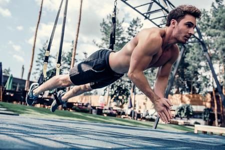 잘 생긴 근육 질의 남자가 TRX에서 야외 훈련을하고 있습니다. 총 신체 저항 운동. 체육관에서 운동. 스톡 콘텐츠