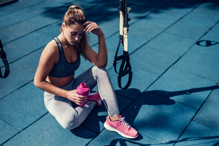 魅力的な若いスポーツ女性は屋外で TRX トレーニングをやっています。休憩を取りながら、手にシェーカーで床に座っています。美しい少女は、ジム 写真素材