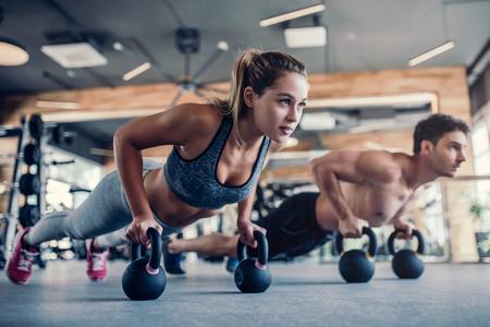 若いカップルがジムで働いています。魅力的な女性とハンサム筋肉の男性は、光現代のジムでのトレーニングです。ケトルベルにプランクを行いま
