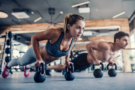 Young couple is working out at gym. Attractive woman and handsome muscular man are training in light modern gym. Doing plank on kettlebell. Push-up on weights. Stock Photo