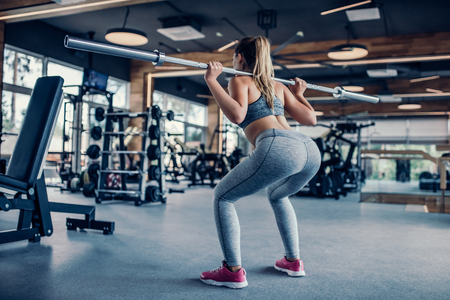 Attractive young sports woman with barbell. Doing squats. Back view of beautiful girl squatting.