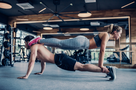 Young couple is working out at gym. Attractive woman and handsome muscular man are training in light modern gym. Double plank. Man is doing plank with girl atop. Lizenzfreie Bilder