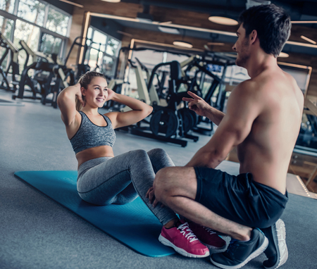 Young couple is working out at gym. Attractive woman and handsome muscular man are training in light modern gym. Abs excercises.