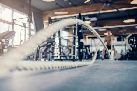 Handsome muscular man is training in gym. Sports man with rope during functional training. Crossfit.