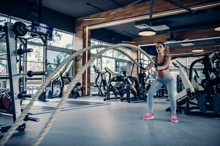 Attractive young sports woman is training in gym. Beautiful girl with rope during functional training. Crossfit.
