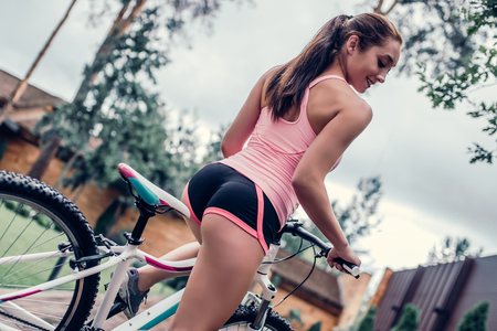 Young sports woman is cycling outdoors in shorts. Attractive girl with bicycle.
