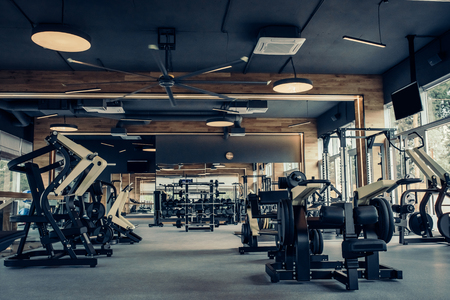 Modern light gym. Sports equipment in gym. Barbells of different weight on rack. Фото со стока