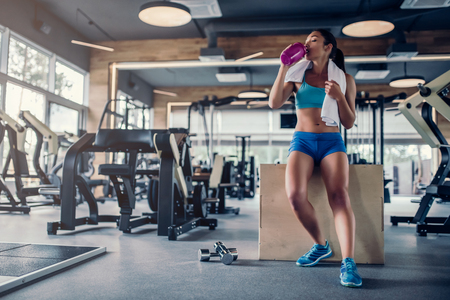 Sports woman in gym. Drinking water while sitting on jumping box. Dumbbells are lying nearby