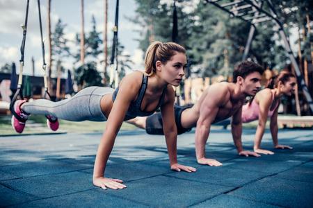 スポーツの人々 のグループは、屋外で TRX トレーニングです。全身の抵抗運動。2 つの魅力的な若い女性とハンサムな男はジムでワークアウトします 写真素材