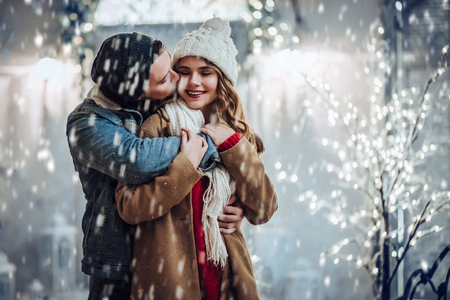 Young romantic couple is having fun outdoors in winter before Christmas. Enjoying spending time together in New Year Eve. Two lovers are hugging and kissing in Saint Valentines Day. Stock Photo