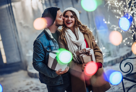 Young romantic couple is having fun outdoors in winter before Christmas. Enjoying spending time together in New Year Eve. Two lovers are hugging and kissing in Saint Valentines Day. Banco de Imagens