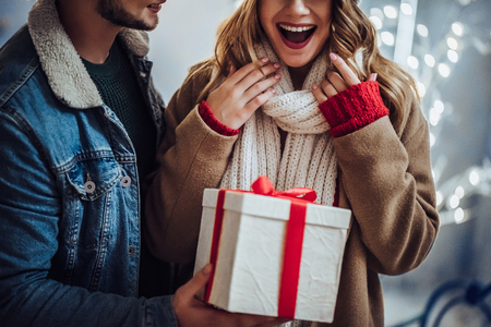Cropped image of young romantic couple is having fun outdoors in winter before Christmas. Enjoying spending time together in New Year Eve. Two lovers are hugging and kissing in Saint Valentines Day.