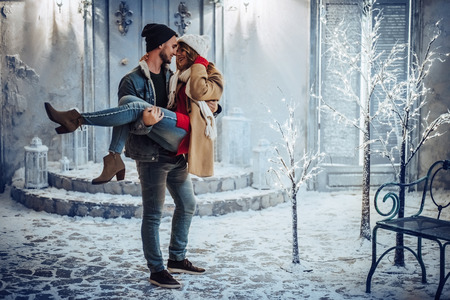 Young romantic couple is having fun outdoors in winter before Christmas. Enjoying spending time together in New Year Eve. Two lovers are hugging and kissing in Saint Valentine's Day. Archivio Fotografico