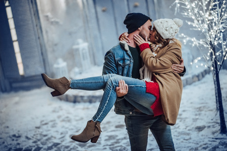 Young romantic couple is having fun outdoors in winter before Christmas. Enjoying spending time together in New Year Eve. Two lovers are hugging and kissing in Saint Valentine's Day. Foto de archivo