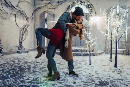 Young romantic couple is having fun outdoors in winter before Christmas. Enjoying spending time together in New Year Eve. Two lovers are hugging and kissing in Saint Valentines Day. Banque d'images