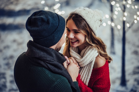 Young romantic couple is having fun outdoors in winter before Christmas. Enjoying spending time together in New Year Eve. Two lovers are hugging and kissing in Saint Valentine's Day. Imagens