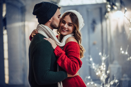 Young romantic couple is having fun outdoors in winter before Christmas. Enjoying spending time together in New Year Eve. Two lovers are hugging and kissing in Saint Valentine's Day. Reklamní fotografie