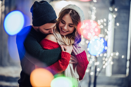 Young romantic couple is having fun outdoors in winter before Christmas. Enjoying spending time together in New Year Eve. Two lovers are hugging and kissing in Saint Valentine's Day. Banque d'images