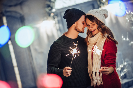 Young romantic couple is having fun outdoors in winter before Christmas with Bengal lights. Enjoying spending time together in New Year Eve. Two lovers are hugging and kissing in Saint Valentine's Day