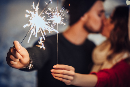 La pareja romántica joven se está divirtiendo al aire libre en invierno antes de la Navidad con las luces de Bengala. Disfrutando pasar el tiempo juntos en Nochevieja. Dos amantes se abrazan y se besan en San Valentín Foto de archivo