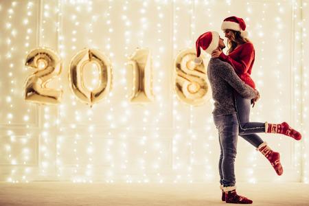 Junges romantisches Paar in Santa Claus-Hüten wartet zu Weihnachten zusammen zu Hause. Umarmen und Küssen im Sylvesterabend auf dem Hintergrund von Girlanden und von Buchstaben 2018. Standard-Bild - 90697129
