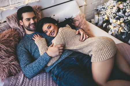 Passionate romantic couple spending time before New Year near beautiful Christmas tree at home