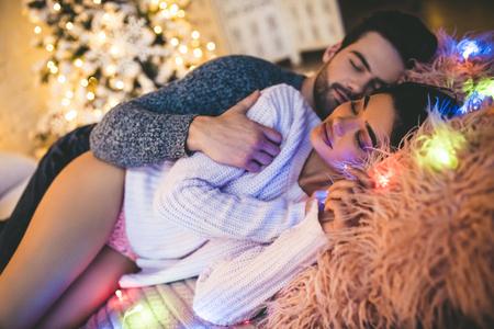 Hartstochtelijke romantische paar het besteden tijd vóór Nieuwjaar dichtbij mooie Kerstboom thuis