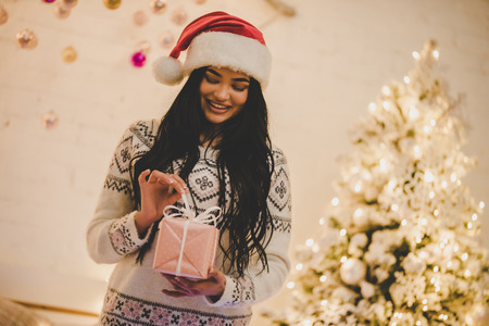 Sexy young woman in sweater and Santa Claus hat is preparing for celebrating New Year at home Stock Photo