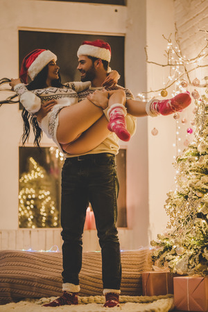 Sexy young woman and handsome man in sweaters and Santa Claus hats are  preparing for celebrating New Year at home. Man is circling the girl in his arms near beautiful Christmas tree. Stock Photo