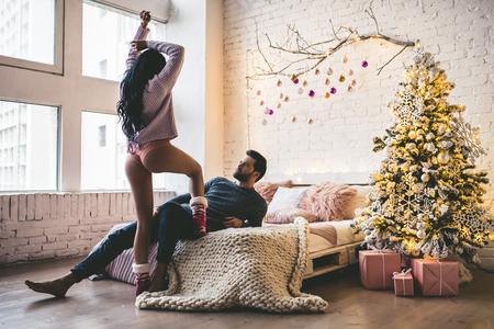 열정적 인 낭만적 인 부부는 새해 전부터 집에서 아름다운 크리스마스 트리 근처에서 시간을 보내고 있습니다. 스톡 콘텐츠