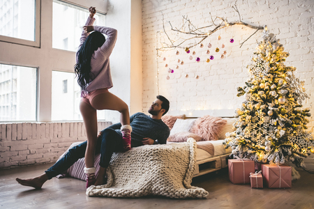 Passionate romantic couple is spending time together before New Year near beautiful Christmas tree at home