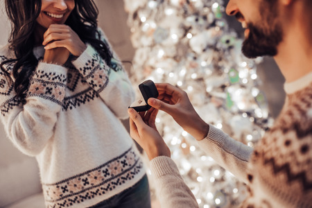 Merry Christmas and Happy New Year! Beautiful couple is waiting for the New Year together near beautiful Christmas tree at home. Handsome man is making proposal to his attractive young woman.