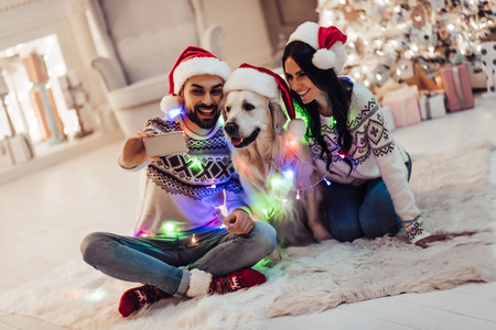 Merry Christmas and Happy New Year! Happy couple with dog labrador retriever waiting for the New Year in Santa Claus hats while sitting near beautiful Christmas tree at home. Smiling and making selfie Stock Photo