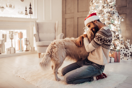Merry Christmas and Happy New Year! Handsome man is sitting near beautiful Christmas tree at home and hugging with dog labrador retriever.
