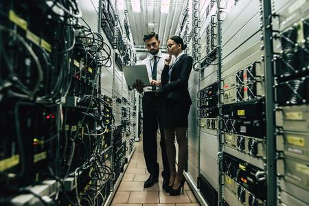 Bel homme et jolie femme travaillent dans le centre de données avec ordinateur portable. Spécialistes en informatique dans la salle des serveurs réseau. Exécution de diagnostics et de maintenance. Techniciens examinant le serveur.