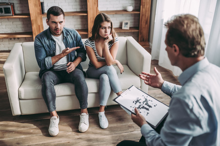 Young couple  at a psychologists reception. Solving family problems. Senior experianced psychotherapist is sitting with Rorschach test.