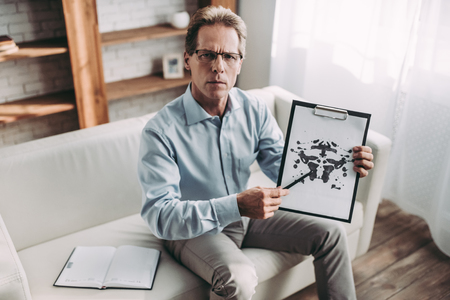 Senior experianced psychologist is sitting on sofa in his office. Holding Rorschach test in hands. Stock Photo