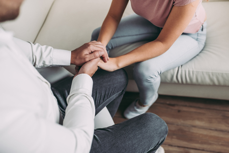 Cropped image of young woman is sitting on sofa during the psychotherapy session. Girl at a psychologists reception. Experianced doctor is sitting nearby and holding patients hands. Stock Photo