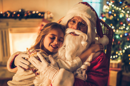Little charming girl with happy Santa Claus in beautiful house decorated for Christmas. Child is sitting on Santas lap and hugging him.