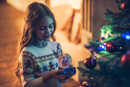 Little cute girl is waiting for Christmas at home. Charming kid is standing with magic ball in New Year Eve.